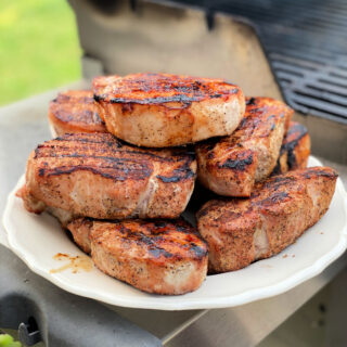 Platter of grilled pork chops next to a gas grill.