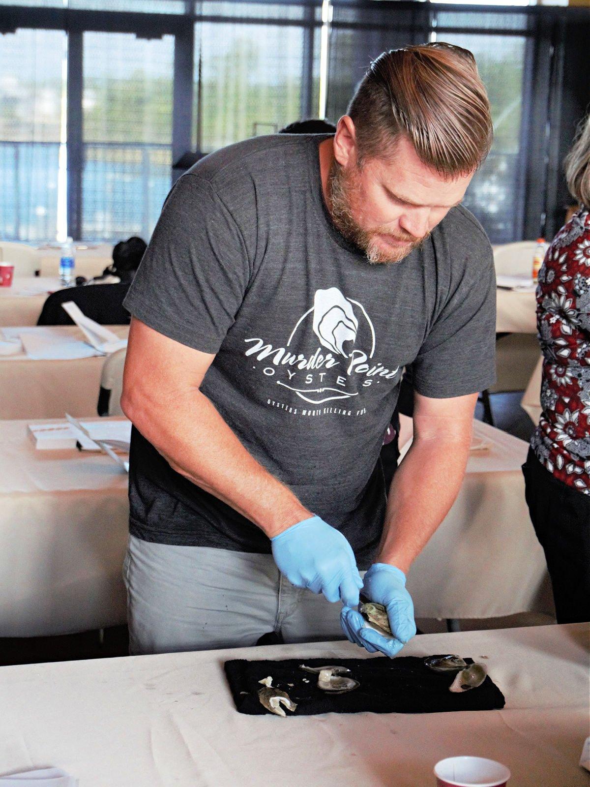 Man wearing a gray shirt shucking oysters.