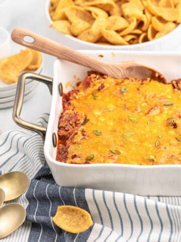 White casserole dish filled with sloppy Joe dip and corn chips on the side.