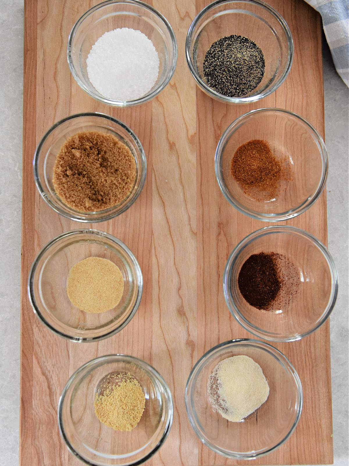 Spices in small glass bowls on top of a wooden cutting board.