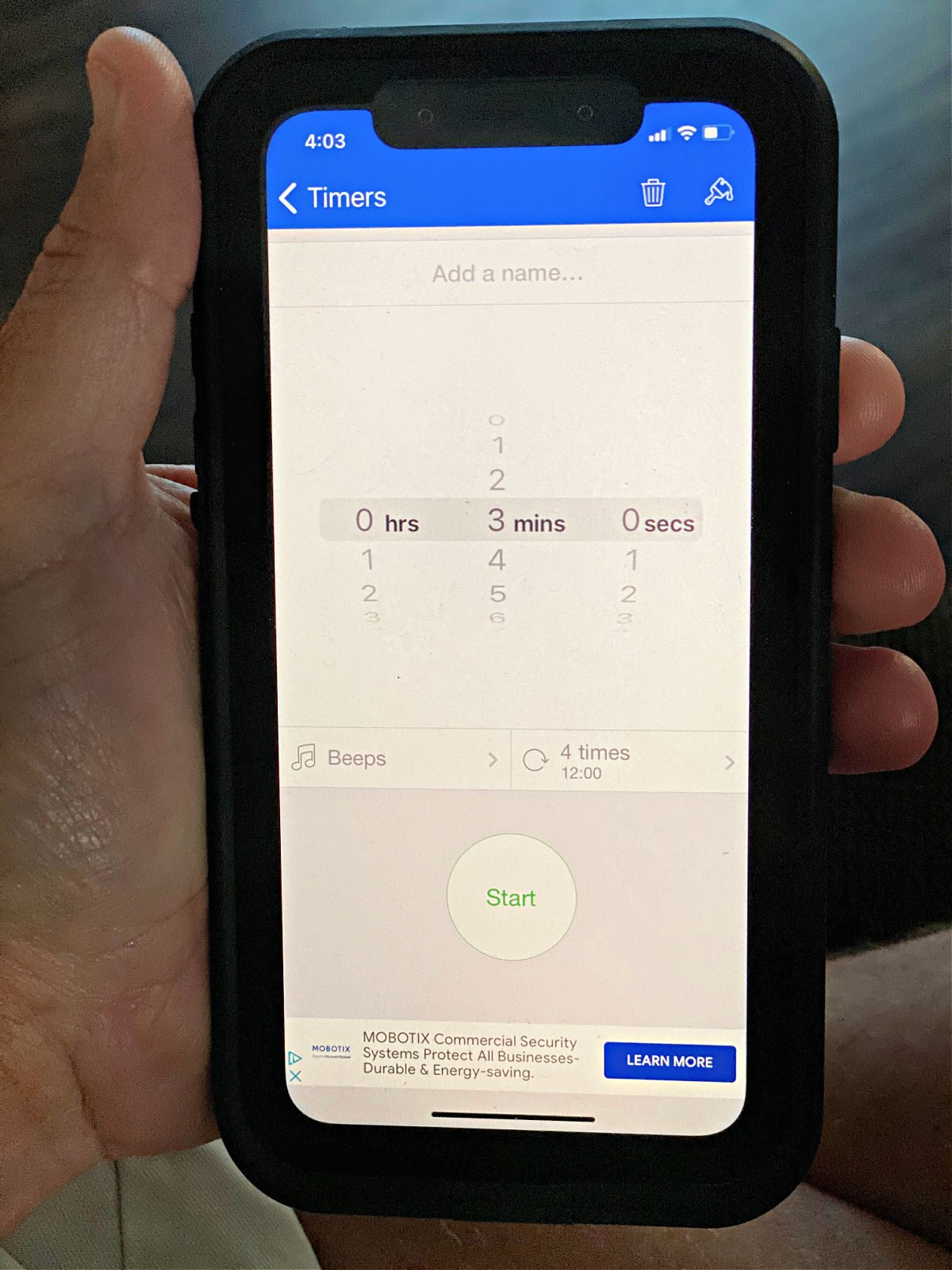 Hand holding an iPhone with a timer app on the screen.