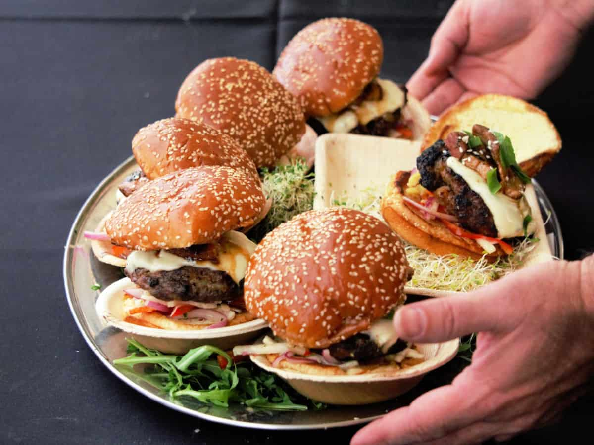 Man holding a platter of hamburgers.