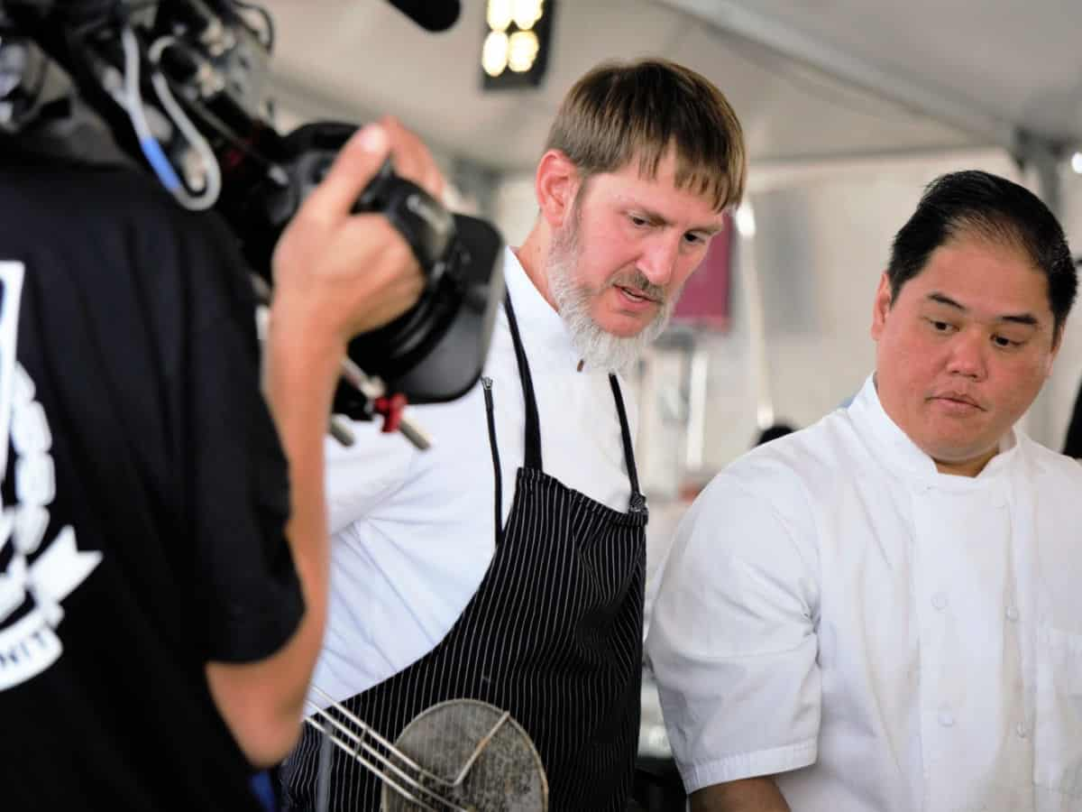 Chefs being filmed at a food competition.