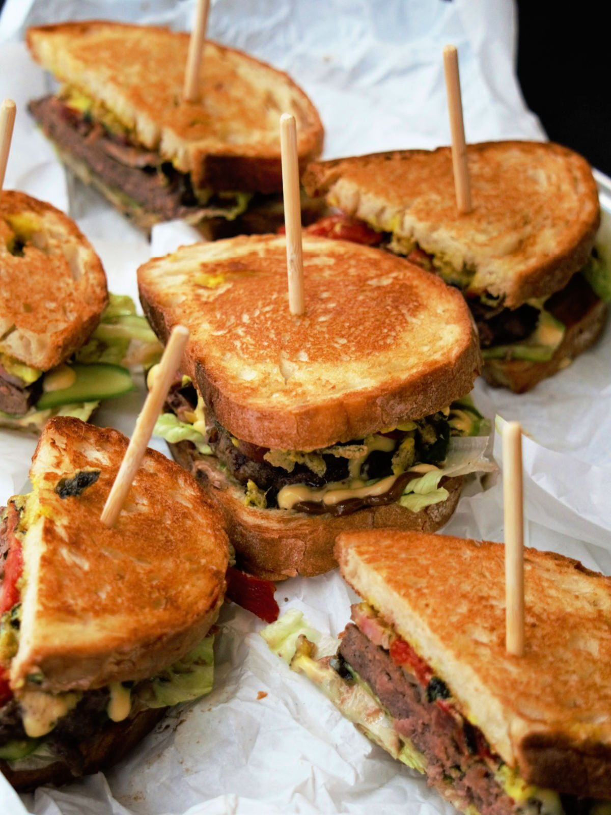 Plate of grilled beef burgers on toasted bread.