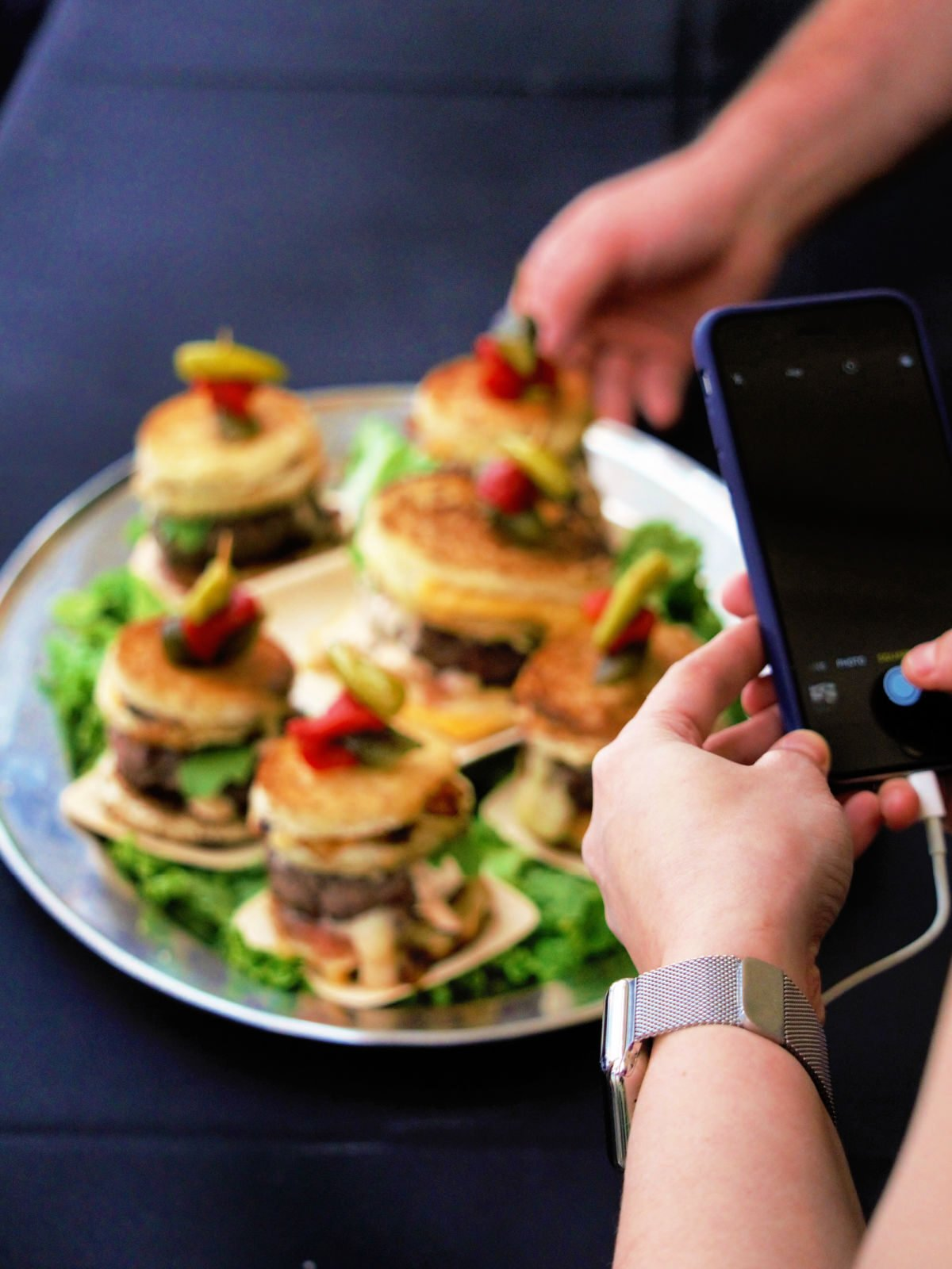 Person taking a photo with a phone of hamburgers.