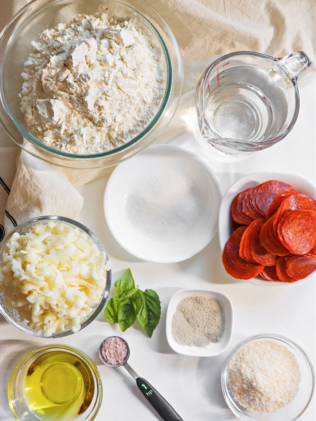 Flour, water, sugar, cheese, pepperoni, yeast and oil for making pizza bites.