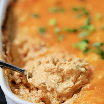 Buffalo dip in a white casserole dish.