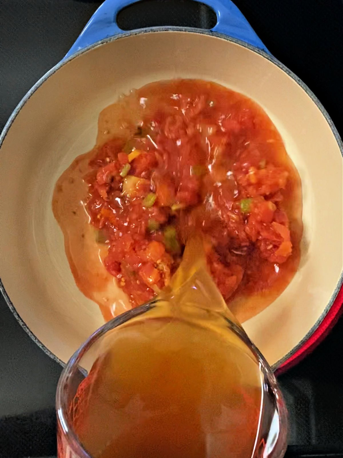 Pouring broth over tomatoes in a Dutch oven.