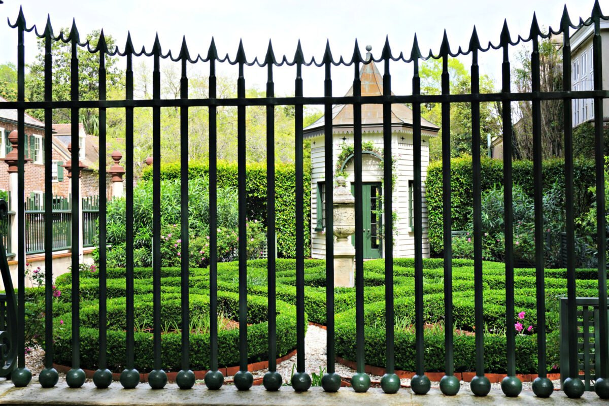 Courtyard surrounded by wrought iron gate.